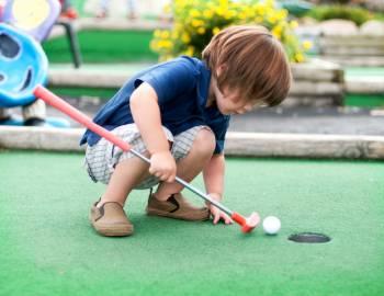 kid playing mini golf